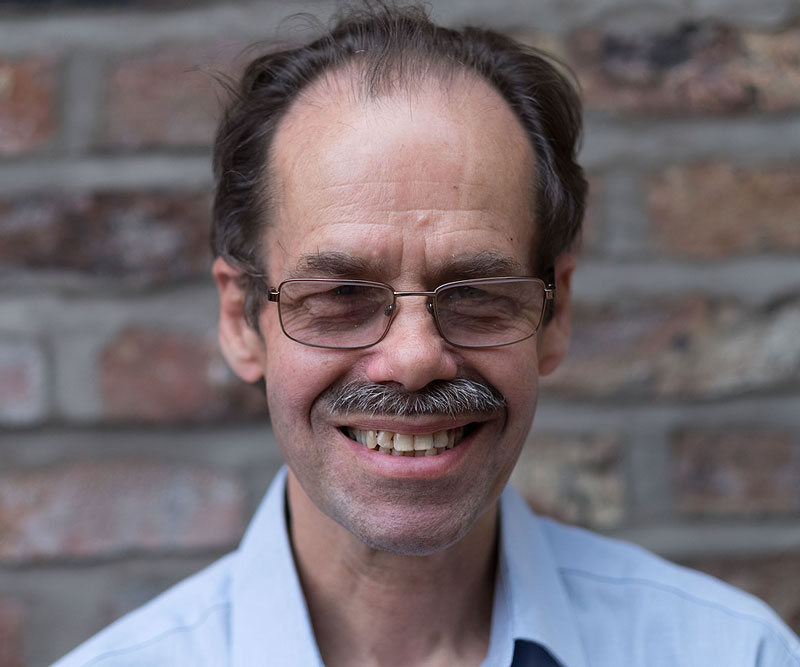 Colour head and shoulders photo of Mike smiling, wearing glasses and an open necked light blue shirt