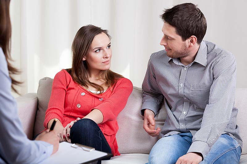 A young heterosexual couple look at each other as they talk to the female counsellor