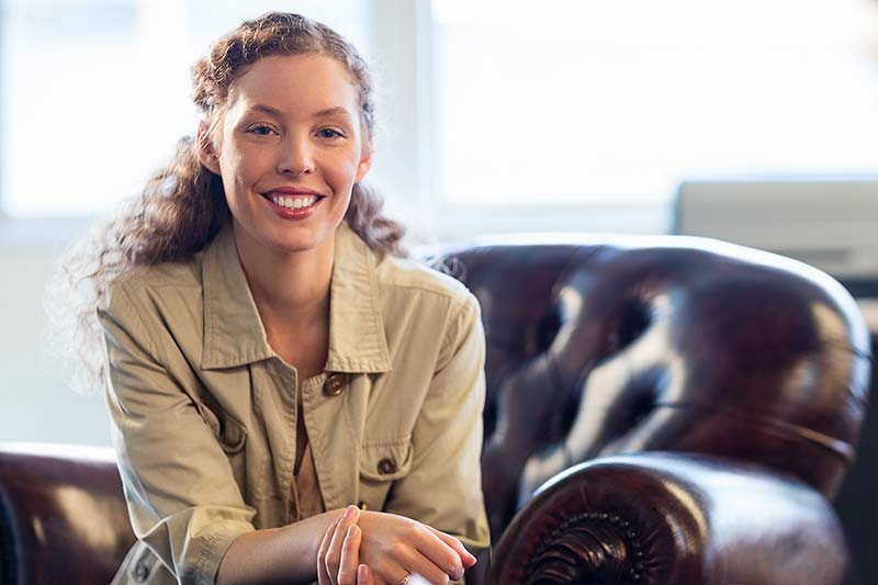 Smiling young woman sitting on a comfortable brown leather chair